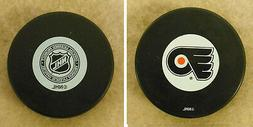 LOT OF 2 HOCKEY PUCKS -NHL OFFICIAL IN GLAS CO - PHILADELPHI